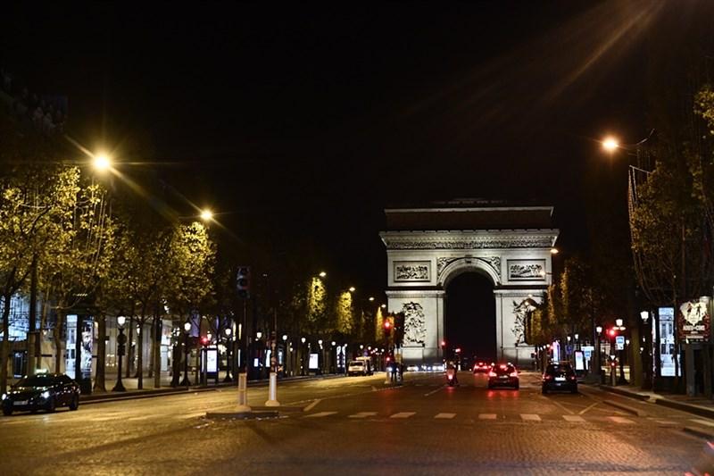 法國至24日累計確診增至108萬6497例排名全球第5高。圖為17日晚間巴黎凱旋門前街道因防疫實施宵禁只見數台車輛經過。(安納杜魯新聞社)