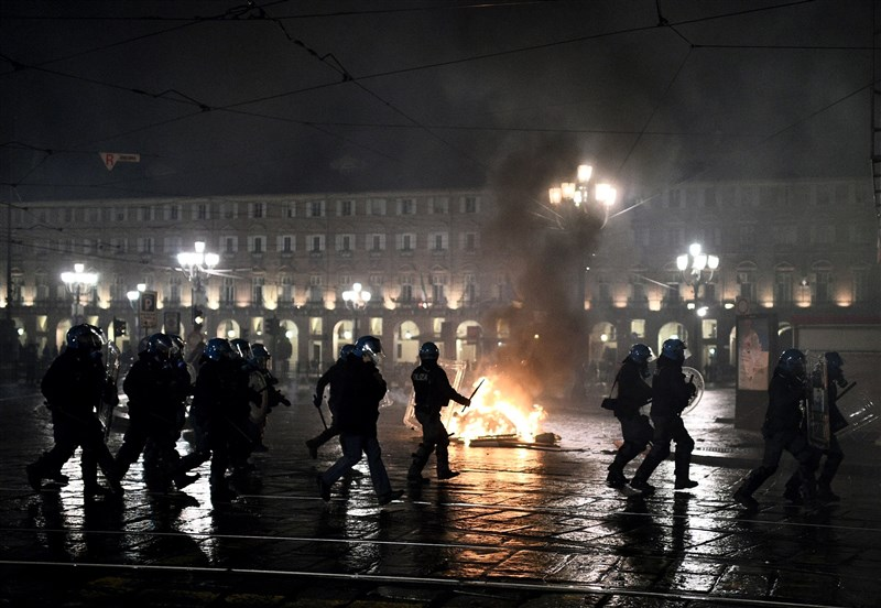 義大利總理孔蒂26日下令餐廳和酒吧須於晚間6時打烊,戲院、電影院、健身房須歇業一個月,引起群眾上街抗議。圖為杜林警察在一處因示威活動而起火的垃圾桶前行動。(法新社)