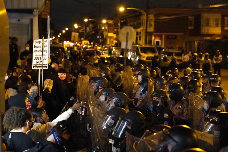 美國非裔男子華勒斯日前遭到警方射殺,數以千計的民眾走上街頭抗議,賓州費城連續兩晚街頭動盪後當地政府決定實施宵禁。圖為27日晚上示威者與鎮暴警察對峙。(美聯社)