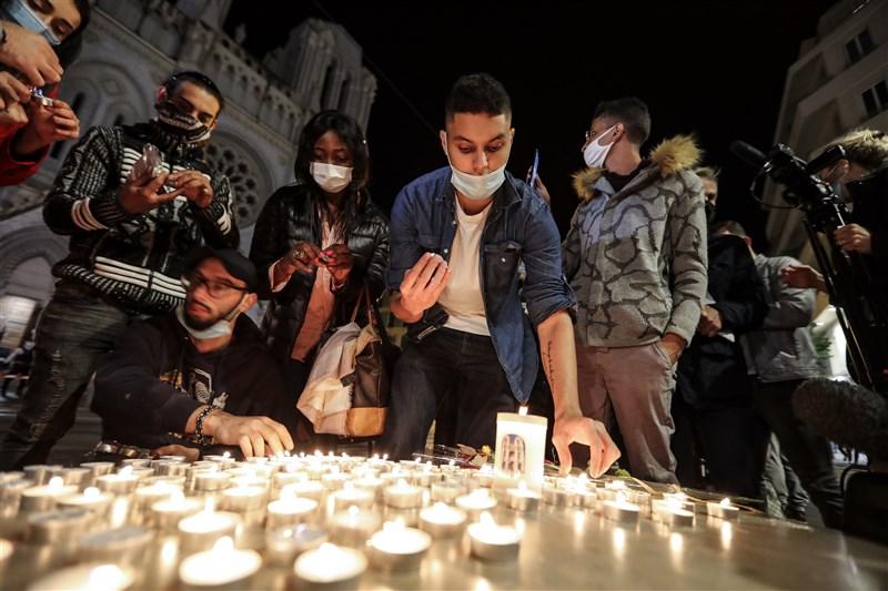 法國29日發生一連串攻擊事件,尼斯天主教堂內發生恐怖攻擊,3人遭殺害;亞維儂、里昂也傳出攻擊者持武器在街上揮舞威脅的事件。圖為民眾在巴黎聖母院大教堂外點燃蠟燭,悼念尼斯攻擊案的3名受害者。(法新社)