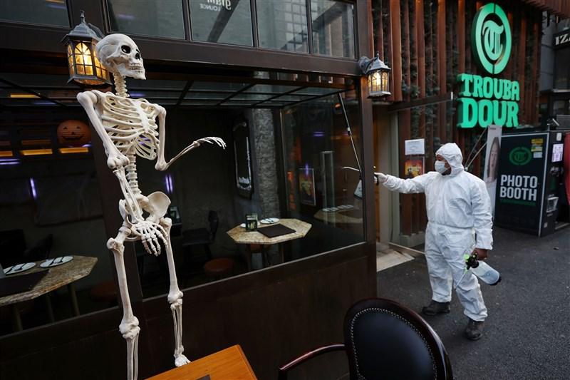 韓國中央防疫對策本部通報,截至30日凌晨零時,新增114例確診。圖為29日首爾梨泰院商圈街頭萬聖節裝飾,防疫人員正進行消毒。(韓聯社)