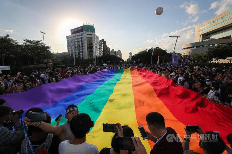 2020第18屆台灣同志遊行31日在台北盛大登場,主辦單位表示,今年有13萬人共襄盛舉,也讓台灣同志遊行成為今年度北半球最大的同志遊行。圖為遊行隊伍抵達終點時,人群圍繞在巨型彩虹旗周邊拍照留念。中央社記者裴禛攝 109年10月31日