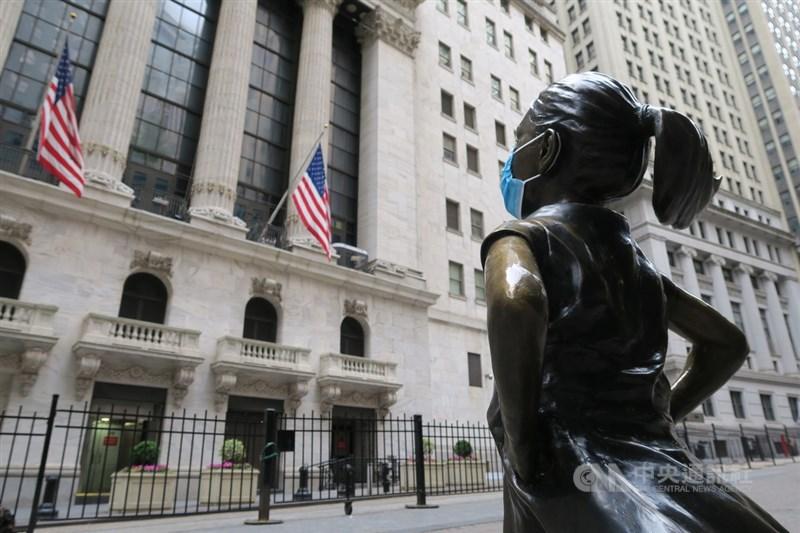 美股30日在科技股拖累下收黑,道瓊工業指數下跌157點。圖為紐約證券交易所與對街戴上口罩的大無畏女孩銅像。(中央社檔案照片)