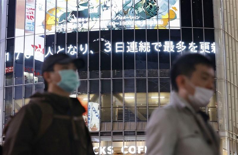 日本境內疫情延燒,14日東京澀谷街頭電子看板顯示日本確診數已連續3天創新高。(共同社)