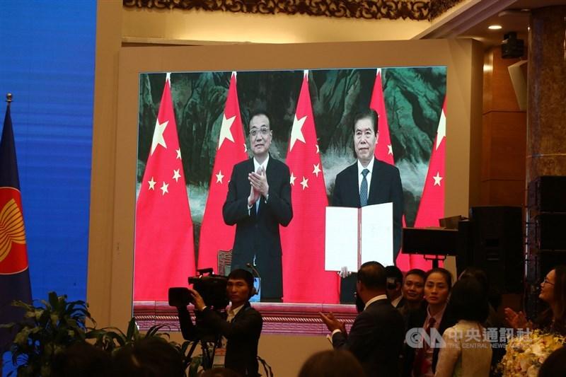 區域全面經濟夥伴協定(RCEP)是世界上最大的自由貿易協定,外界一般認為中國在背後主導談判。圖為中國國務院總理李克強(左)及中國商務部部長鍾山15日以視訊方式參與RCEP簽署儀式。中央社記者陳家倫河內攝 109年11月15日