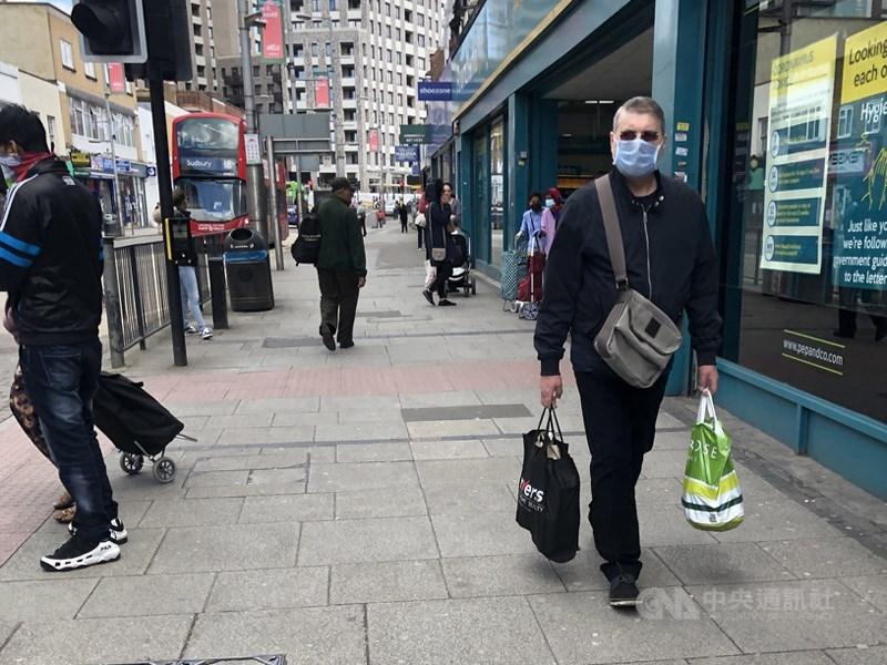 英國牛津大學研究人員表示,曾感染武漢肺炎的人,至少6個月內不太可能再次染疫。圖為5月英國倫敦民眾戴口罩上街採買。(中央社檔案照片)