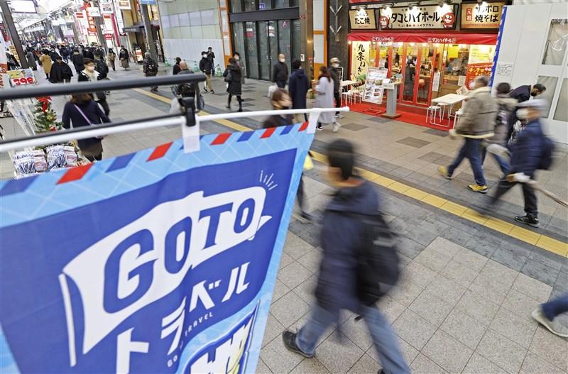 日本首相菅義偉23日否認疫情升溫跟振興旅遊方案有關。圖為北海道札幌狸小路商店街上懸掛振興旅遊(Go To Travel)宣傳旗幟。(共同社)