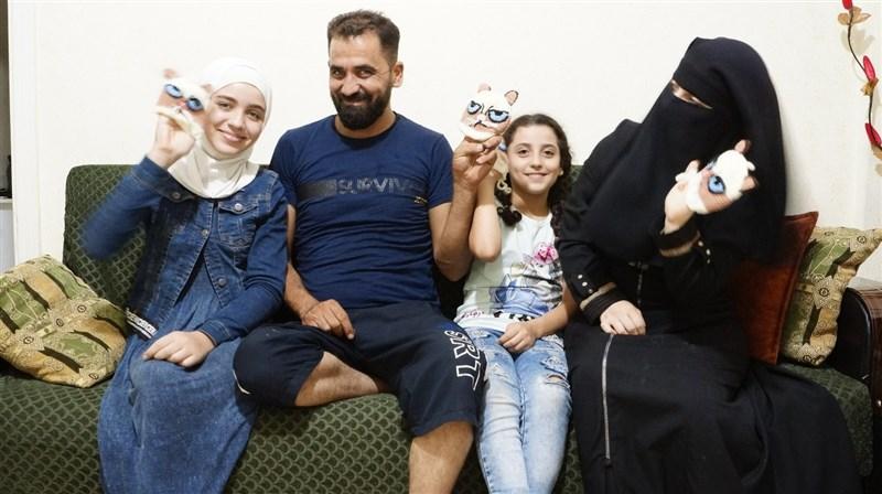 敘利亞母親「藍眼喵喵」(右1)設計和編織澡袋參與義賣,為遭戰火炸斷左腿的大女兒(左1)籌手術費。圖為一家人展示「藍眼喵喵澡袋」。(裘振宇提供)中央社記者何宏儒安卡拉傳真 109年11月29日