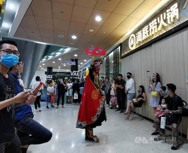 胡志明市一名英文老師在越南境內感染武漢肺炎後,當局已要求逾10萬名大學生停課在家。圖為火鍋業者在胡志明市商場中表演川劇變臉,多數民眾戴著口罩。中央社記者陳家倫胡志明市攝 109年12月1日