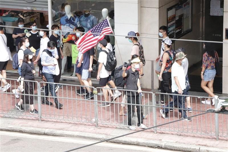 香港泛民主派多名代表人物,包括民主黨前主席胡志偉和社會民主連線副主席梁國雄等人8日上午被捕,警方指他們涉及「七一」遊行多項罪行。圖為港區國安法生效後的第一個「七一」紀念日,民眾自發上街在銅鑼灣崇光百貨一帶等多個地點示威,其中有人舉起美國國旗。(中央社檔案照片)