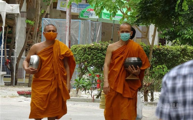 泰國向英國製藥公司購買武漢肺炎疫苗,希望藉由大規模接種計畫,讓泰國可以盡快迎回國際觀光客,重振泰國經濟。圖為泰國寺廟僧侶戴上口罩,托著缽準備前往食堂用餐。(中央社檔案照片)