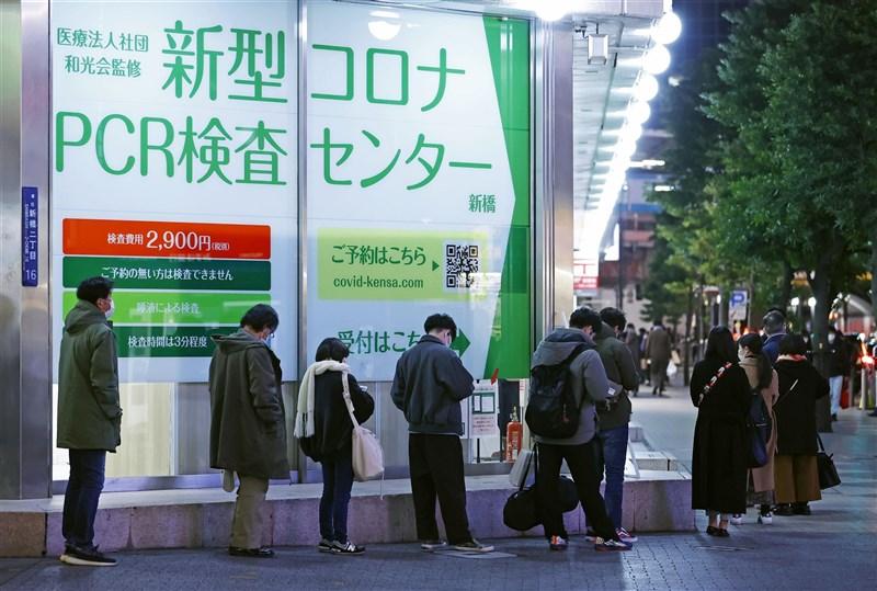 日媒報導,日本除了機場檢疫發現5人感染武漢肺炎變種病毒株,26日又通報新病例。圖為26日民眾在東京新橋排隊等候病毒篩檢。(共同社)