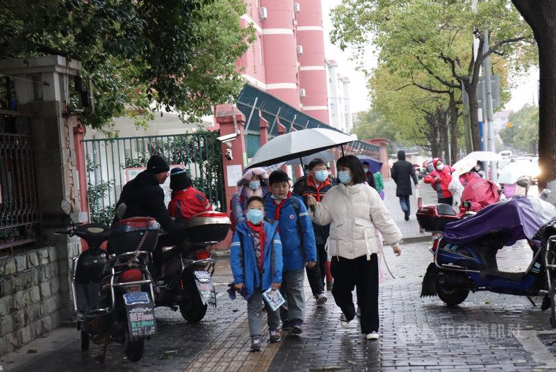 中國大部分地區從28日至31日遭受今年入冬以來最強寒流,醫生提醒注意保暖、老人少出門。圖為29日下午,上海一小學外家長接送學童的景象。中央社記者張淑伶上海攝 109年12月29日