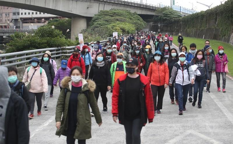 台灣未來半年仍處武漢肺炎防疫期,業者表示,口罩短期恐難回到以前每盒百元以下價位。圖為元旦健走活動。(中央社檔案照片)