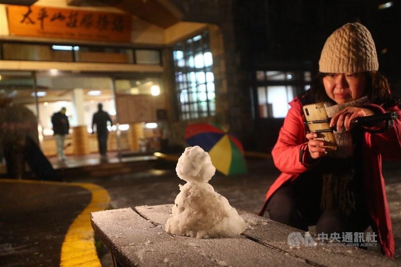 寒流襲台,太平山國家森林遊樂區7日晚間開始下雪,太平山莊前有遊客堆起小雪人,吸引眾人拍照留念。中央社記者王騰毅攝 110年1月7日