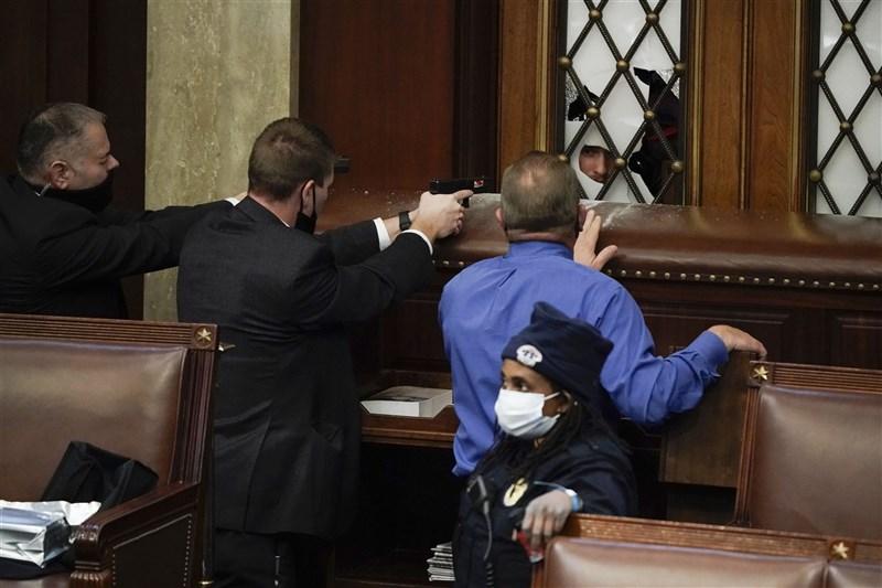 美國總統川普的部分支持者6日闖入國會大廈,眾院議場的執法人員拔槍警告入侵者。(美聯社)