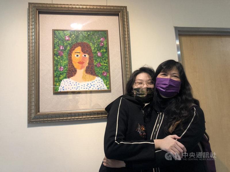 罹患罕見疾病的于昕蕎(左)在童綜合醫院舉辦畫展,8日在畫作前與母親相擁,以畫作傳遞對母親滿滿的愛。中央社記者趙麗妍攝 110年1月8日