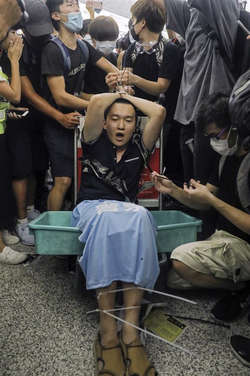 香港3名「反送中」運動示威者,被控於2019年8月在香港國際機場禁錮和襲擊中國大陸環球時報記者付國豪(前中),法庭8日宣判,3人分別判處入獄4年3個月至5年半不等。圖為付國豪被示威者用索帶綁在機場行李車上。(美聯社)