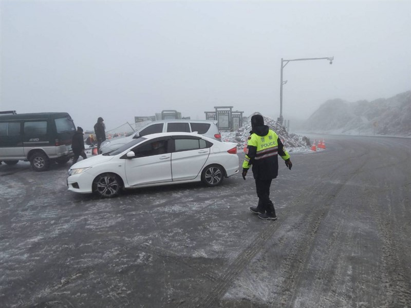 合歡山因寒流來襲下雪,路面結冰,台14甲線29公里處,也就是昆陽停車場往鳶峰方向,大轉彎處路面結冰比較厚,即使小型車加掛雪鍊也很難開到昆陽停車場。圖為南投警方指揮上山車輛情形。(翻攝照片)中央社記者吳哲豪傳真 110年1月9日