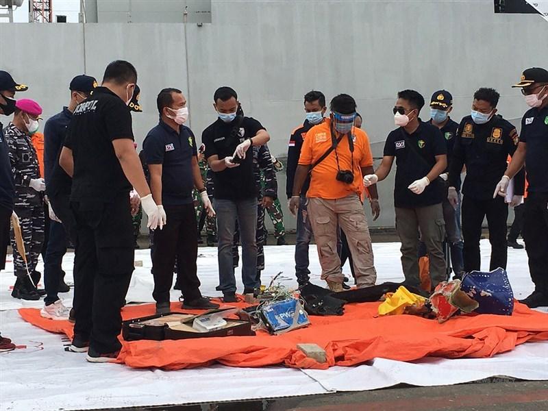 印尼搜救人員10日在雅加達國際貨櫃碼頭的搜救指揮中心檢視從海底尋獲疑似墜海班機的機身及乘客物品。中央社記者石秀娟雅加達攝 110年01月10日