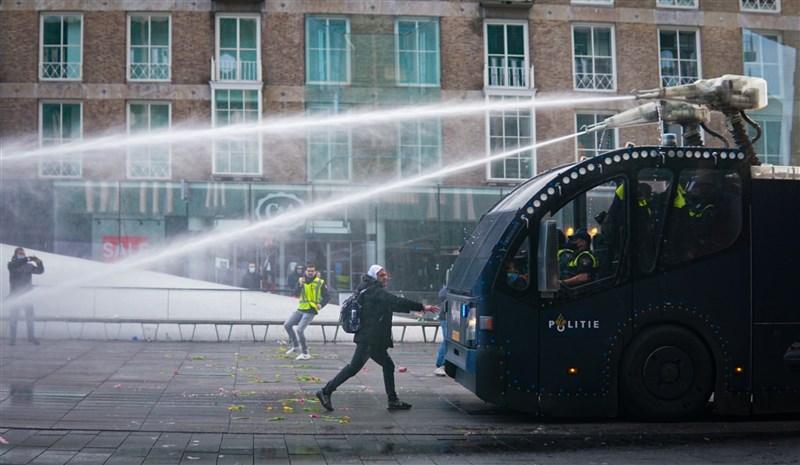 荷蘭政府祭出新防疫宵禁令,各地爆發抗議潮。隨著活動升級為騷亂,總理呂特25日譴責是暴力犯罪。圖為愛因霍芬市上演大規模抗議活動,警方出動催淚瓦斯驅離群眾。(安納杜魯新聞社)