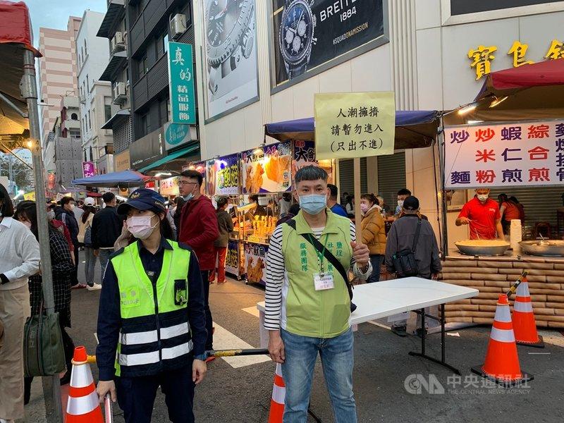 高雄市新樂街市集12日爆量逛街民眾,高市府衛生局緊急派員舉牌「只出不進」管制。中央社記者王淑芬攝 110年2月12日