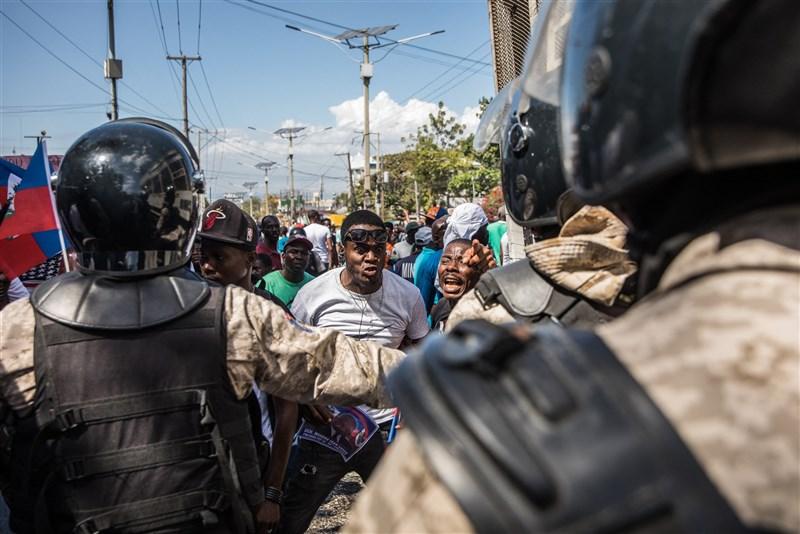 海地數以千計民眾14日在首都太子港示威,指控政府試圖建立新的獨裁政權。圖為示威者與警方對峙。(法新社)