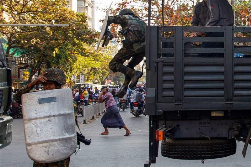 緬甸軍隊近日已部署到全國,15日在瓦城發射橡膠子彈驅散示威群眾,數小時後當局就再度切斷網路連線。圖為15日在瓦城示威發生衝突,士兵從車上跳下、民眾奔跑離開現場。(法新社)