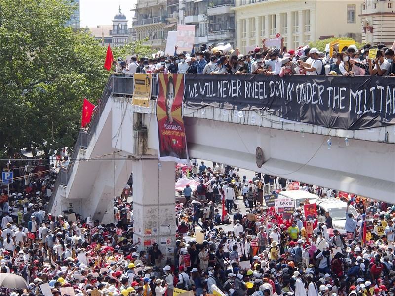 緬甸軍方針對呼籲罷工、癱瘓政府部門的6位名人發布通緝令,當地至今有近500人遭逮捕。圖為仰光民眾17日上街示威。(共同社)