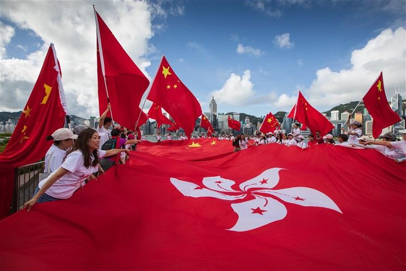 香港當局自2020年底起要求公務員以宣誓或簽署聲明形式,表態擁護基本法及效忠香港特別行政區,目前仍有近200人拒絕簽署。圖為2020年7月1日香港市民揮動中國國旗和區旗。(中新社)
