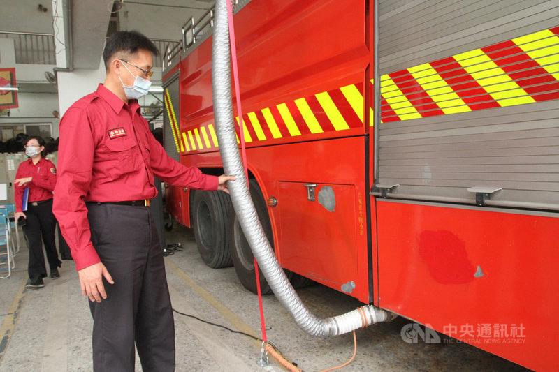 台南市政府消防局設計的智能排氣供電車庫系統,把管線接到消防車的排氣管後,將廢氣排到室外,消防車開出車庫時風管接頭會自動脫落,24日在永康分隊啟用。中央社記者楊思瑞攝 110年2月24日