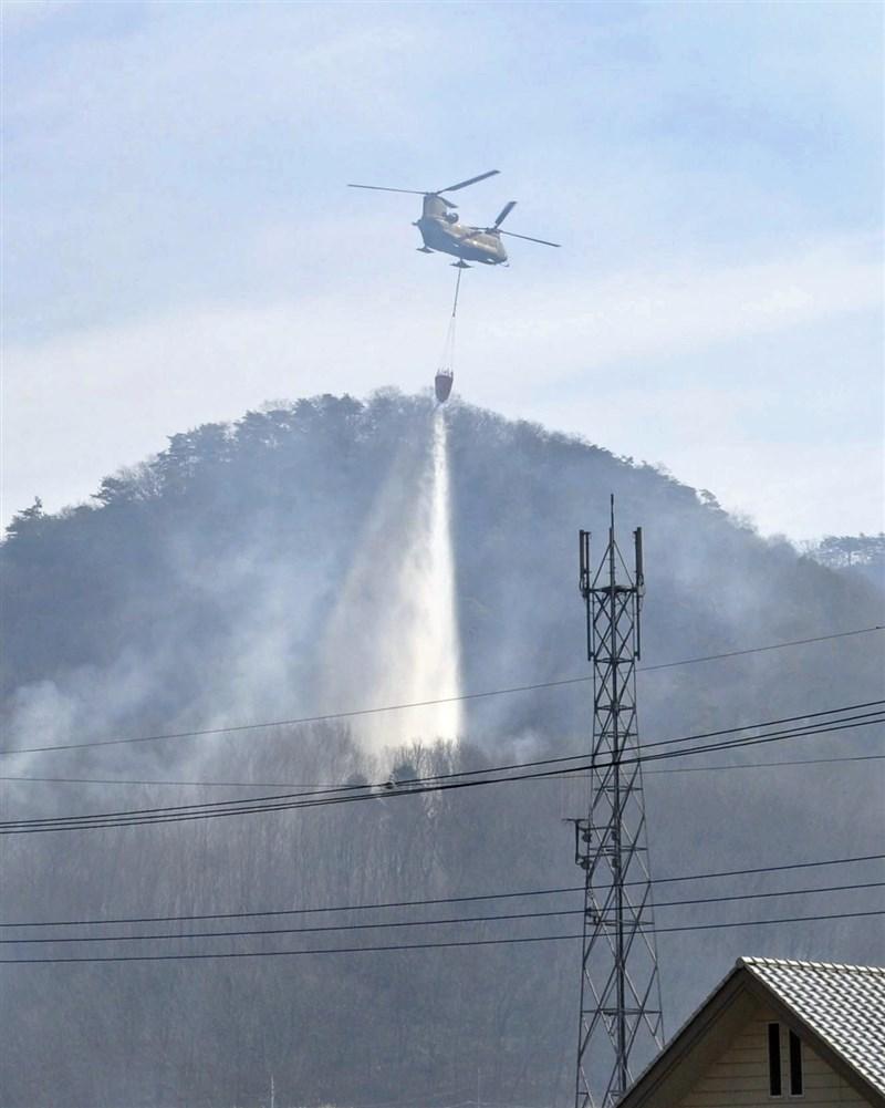日本櫪木縣足利市山林火災至25日止已延燒4天,自衛隊出動直升機從空中灌救。(共同社)