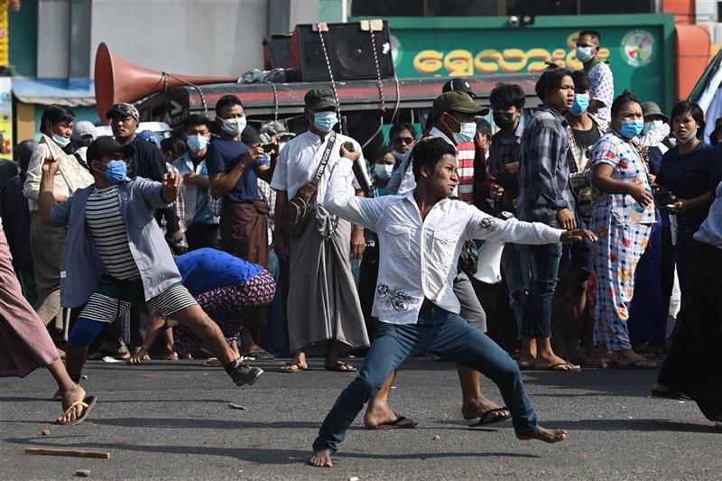 緬甸軍方支持者25日揮舞著刀子和彈弓與仰光的居民發生衝突,境內緊張局勢升溫。圖為軍方支持者投擲武器攻擊仰光居民。(法新社)