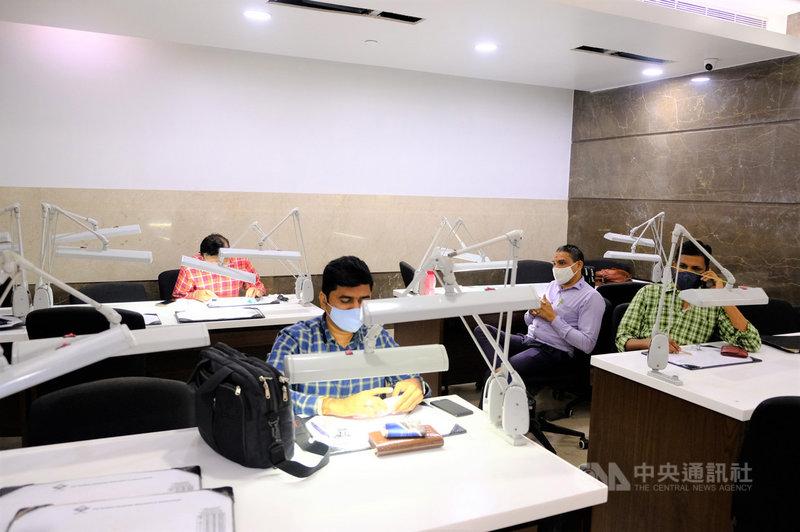 孟買鑽石商協會每天都有許多會員在配備齊全的辦公桌檢測鑽石成色與評估價值。此圖為110年2月24日拍攝。中央社記者康世人孟買攝  110年2月27日