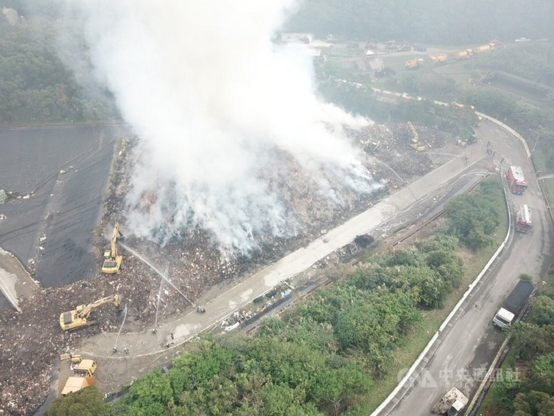 八里大型家具臨時堆置場2月28日起火燃燒,消防局表示,火勢雖撲滅,但內部悶燒中產生濃煙,目前已擴大灑水,積極進行殘火處理。(翻攝照片)中央社記者王鴻國傳真 110年3月1日