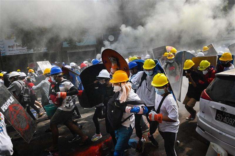 儘管軍警開槍驅離示威者,3日仍有大批緬甸民眾聚集仰光抗議軍方政變。圖為緬甸民眾手持自製盾牌於仰光反政變示威中。(法新社)