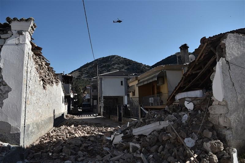 希臘中部3日發生規模6.3強震,造成上百棟建築受損。圖為一台軍用直升機飛過震央附近的達馬西村。(法新社)