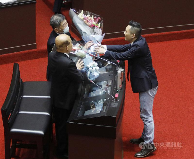 國民黨立委陳以信(右)5日在立法院會質詢時,特別送上花束給一同備詢的行政院長蘇貞昌(左前)與衛福部長陳時中(左後)。中央社記者施宗暉攝  110年3月5日