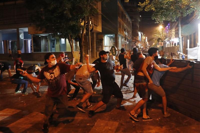 南美洲友邦巴拉圭政府因防疫不力,造成民怨沸騰,5日晚間大批抗議民眾走上街頭,與警方爆發激烈衝突。圖為抗議民眾向警察丟擲石塊。(美聯社)