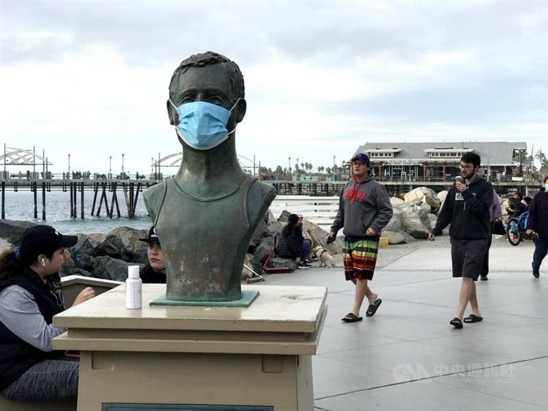 美國參議院6日以50票贊成和49票反對,表決通過1.9兆美元紓困法案。圖為南加州疫情嚴重,芮當多海灘傳奇救生員佛利斯雕像也戴上口罩。中央社記者林宏翰洛杉磯攝 110年1月5日