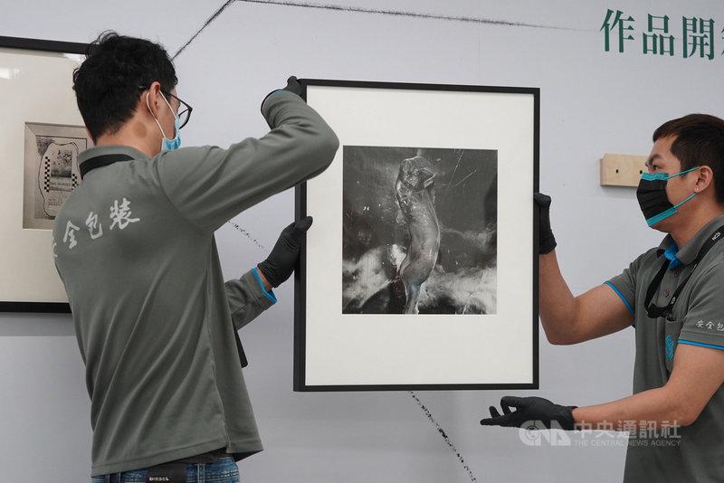國家攝影文化中心台北館8日舉行首檔國際展「塵與時:從宇宙到居所」開箱記者會,工作人員小心翼翼搬出攝影家東松照明的作品。中央社記者徐肇昌攝 110年3月8日