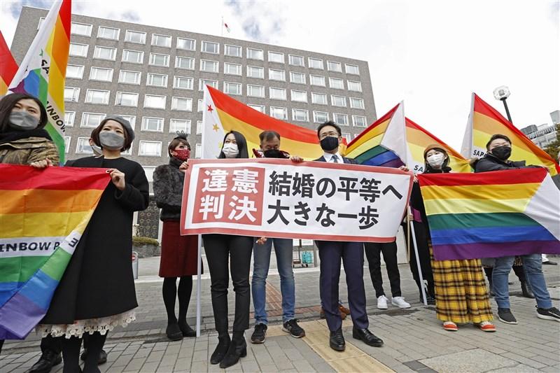 札幌地方法院17日一審判決日本政府不承認同性婚姻違憲,原告辯護律師與支持者在法院前舉出「婚姻平權跨出重大一步」布條。(共同社)