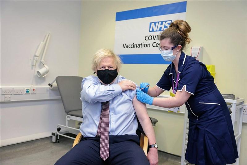 英國施打2019冠狀病毒疾病疫苗達成新里程碑,境內超過半數成人已施打至少一劑疫苗。圖為英國首相強生(左)19日施打阿斯特捷利康疫苗。(圖取自facebook.com/borisjohnson)