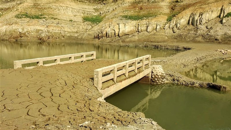 中南部水情告急,苗栗縣永和山水庫18日蓄水率已不到10%,就連隱身庫底約40年的一座「永安橋」也首次重見天日。(林桔春提供)