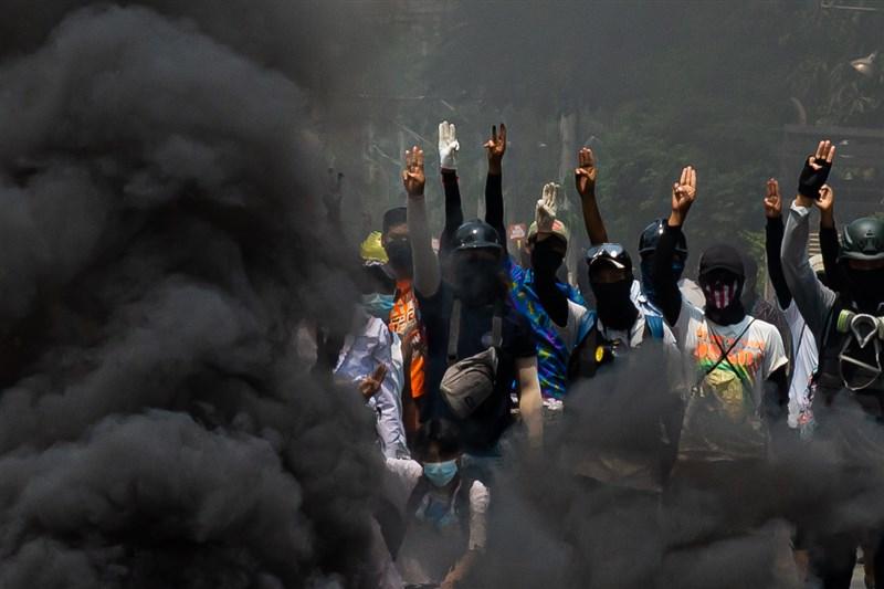 根據媒體及目擊者的說法,緬甸安全部隊27日在全國各地殺害了至少114人,這是緬甸2月1日軍事政變引發抗議以來最血腥的日子。圖為27日仰光街頭示威民眾在燃燒輪胎的煙霧中高舉象徵追求民主的手勢。(安納杜魯新聞社)