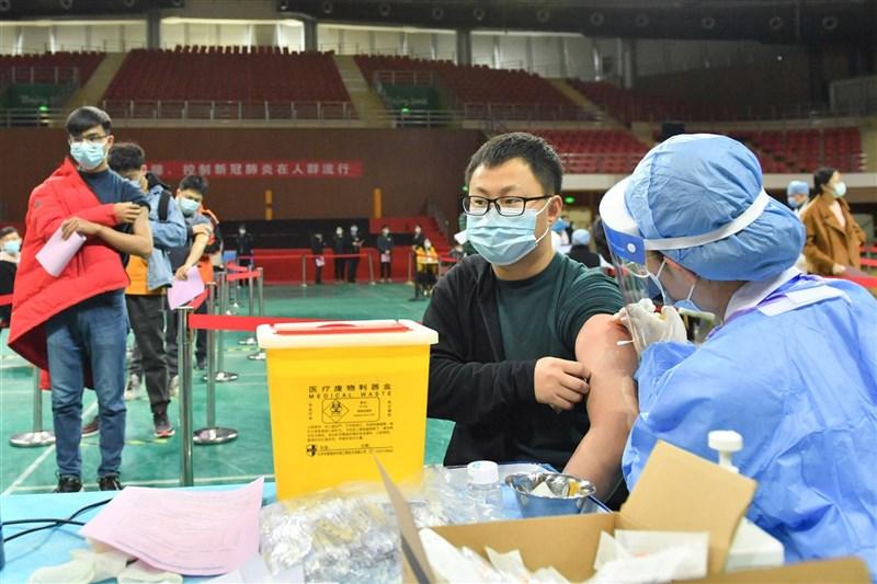 疫情指揮中心陸續討論邊境鬆綁策略,指揮中心27日說,僅承認入境者接種中國疫苗事實,不會改變不採購中國疫苗政策。圖為24日北京理工大學學生接種疫苗。(中新社)