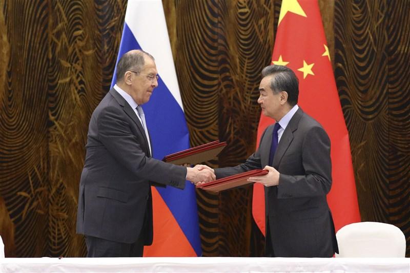 阿拉斯加會談後,中國外交部長王毅(右)會晤俄國外長拉夫羅夫(左),並出訪中東六國,有分析認為,北京正在組成全球統一戰線。(安納杜魯新聞社)