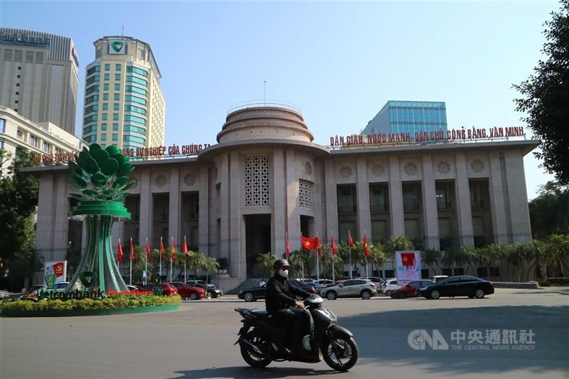 截至台灣3月31日晚間7時,全球至少280萬5004人染疫死亡。圖為3月30日民眾戴口罩騎機車經過越南國家銀行(SBV)。(中央社檔案照片)