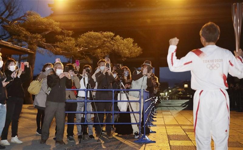 東京奧運聖火正在日本各地傳遞,6日將進入愛知縣半田市,有一段乘船路線依傳統「僅限男性」,因而引發爭議。圖為日本前滑雪選手荻原健司(右)1日在長野縣善光寺接棒聖火。(共同社)