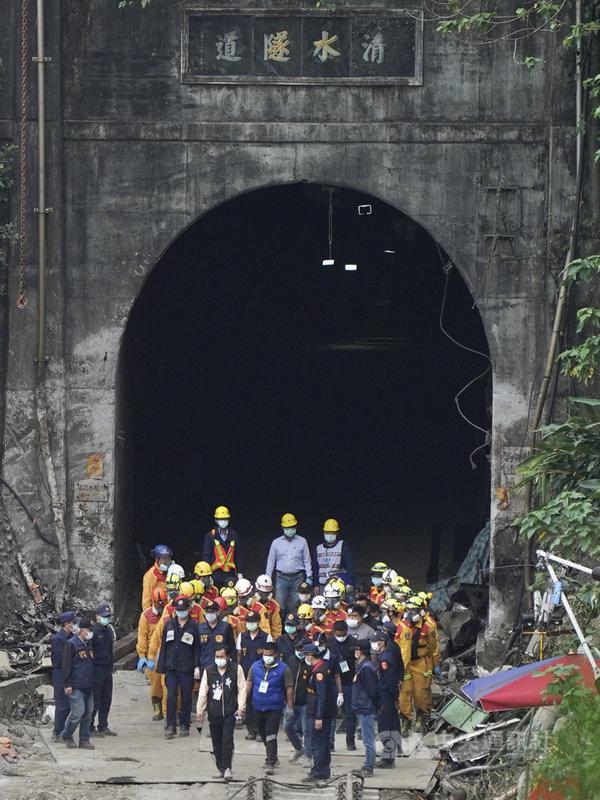 台鐵太魯閣號撞吊卡車嚴重出軌事件,搜救人員5日將壓在第6節車廂下的罹難者救出,大批人員團團圍住遺體走出隧道。中央社記者徐肇昌攝 110年4月5日